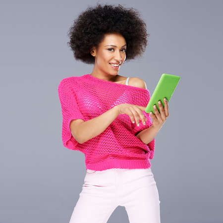 Sexy African American woman in a fashionable trendy pink blouse standing smiling with a tablet in her hands on a grey  photo