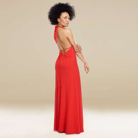 Elegant African American woman with an afro hairstyle posing in a red evening gown standing sideways looking over her shoulder photo