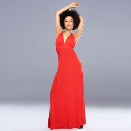 above head: Graceful beautiful young African American woman in a r long ed gown standing with her arms raised above her head against a grey with copyspace