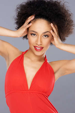 american sexy: Beautiful sexy African American woman with a wild afro hairstyle posing with her hands to her temples looking st the camera with parted lips