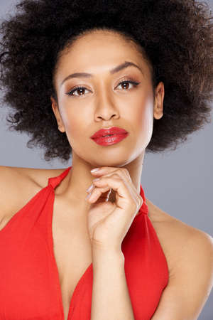 Beautiful pensive African American woman in a stylish red dress looking thoughtfully at the camera with her hand to her chin, close up portrait of her face photo