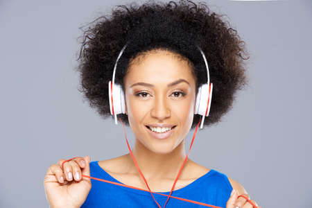 Trendy attractive young African American woman listening to music on a set of headphones smiling at the camera isolated on grey