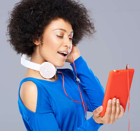 interactivity: Beautiful African American woman with her music standing with the earphones around her neck listening to one and holding her storage device Stock Photo