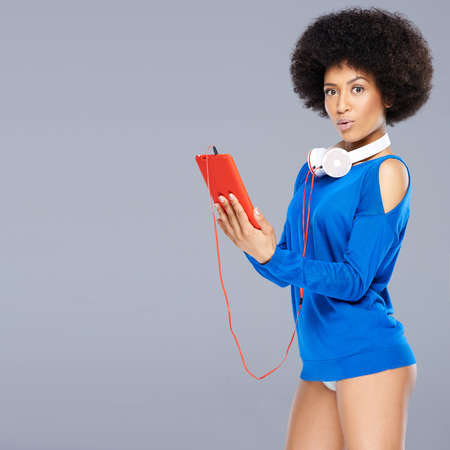 interactivity: Stunning African American woman with a curly afro hairstyle wearing only a blue top posing with a flirtatious look holding a music storage device with headphones around her neck on grey with copyspace Stock Photo