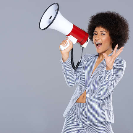 authoritative woman: Vivacious beautiful African American woman holding a megaphone in her hand gesturing at the camera with an excited animated expression