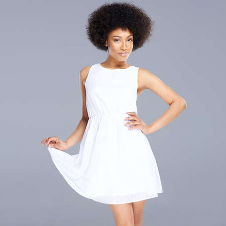 casual dress: Beautiful feminine African American woman in a fresh white short summer dress posing holding up one edge of the flared skirt with a smiling provocative expression, on grey