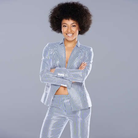 slack: Beautiful glamorous Afro-American woman in a stylish tailored striped slack suit standing looking at the camera with folded arms and a confident amused expression