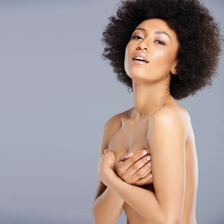 afro american nude: Upper body portrait of a beautiful nude African American woman protecting her breast with her hand posing sideways and turning to smile at the camera, on grey Stock Photo