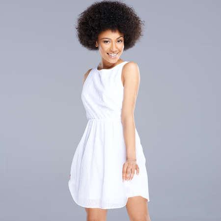 american sexy: Красивая молодая счастливым афро-американских женщина в свежем короткое белое платье, улыбаясь в камеру, квадратного формата на сером
