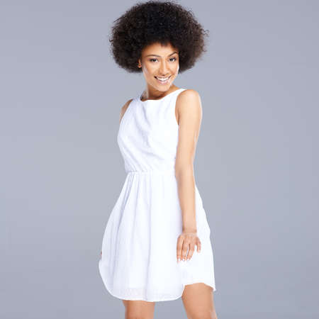 Beautiful young happy African American woman in a fresh short white dress smiling at the camera, square format on grey photo