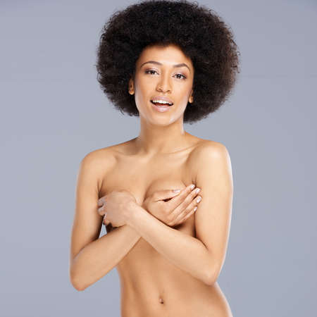 bare breasts: Beautiful sexy nude young Afro-American woman with an large curly afro hairstyle posing seductively with her hands holding her breasts as she faces the camera, upper body portrait