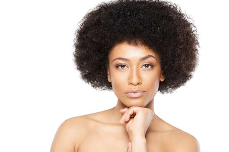 afro hairdo: Beautiful serene African American woman with bare shoulders and a large afro hairdo looking directly at the camera, head and shoulders portrait on grey