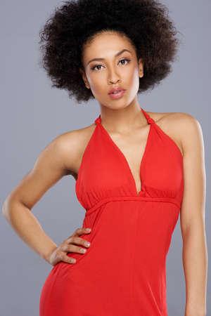 mujer elegante: Glamorous hermosa mujer afroamericana con un cuerpo bien proporcionado sexy en un vestido rojo con estilo que presenta con su mano en la cadera Foto de archivo