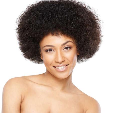 Belle souriante femme afro-américaine avec une coiffure afro bouclés mignon posant avec épaules nues en regardant la caméra avec une expression douce, isolé sur blanc