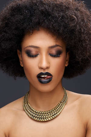 Beautiful seductive African American woman with bare shoulders wearing a gold choker posing with her lips parted and the tip of her tongue showing and downcast eyes Stock Photo