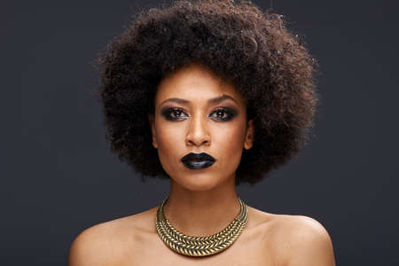 thoughtful woman: Beautiful exotic African American woman with a curly afro hairstyle wearing dark makeup and a gold choker looking directly at the camera with a serious thoughtful expression