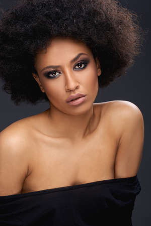 bare shoulders: Beautiful glamorous Afro-American woman with a frizzy afro hairdo and bare shoulders