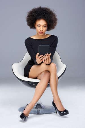 tacones negros: Elegante hermosa mujer afro-americana con un vestido negro elegante y tacones altos sentado en un sillón moderno leyendo la pantalla de su Tablet PC