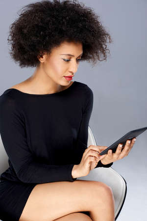interactivity: Vivacious chic African American woman with a wild afro hairdo posing in a glamorous see through pink top with a tablet tucked into the waistband of her slacks smiling at the camera Stock Photo