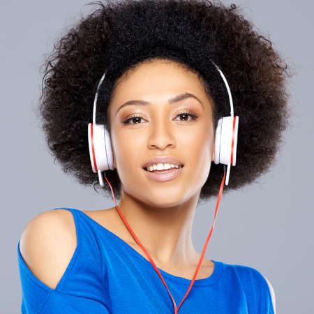 Gorgeous beautiful young African American woman with a frizzy afro hairstyle listening to music on her earphones looking at the camera with a dreamy expression photo