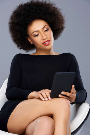 interactivity: Beautiful elegant African American businesswoman sitting reading her tablet in a comfortable modern design armchair
