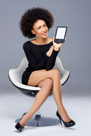 Smiling beautiful elegant young African American woman showing her blank tablet screen to the camera as she its in a stylish modern armchair