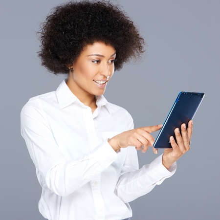 interactivity: Attractive Afro-American woman with a curly afro hairstyle wearing stylish clothes holding a tablet computer as she surfs the internet, on grey