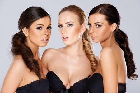 그들은 그룹에서 함께 포즈로 카메라를 다루고 찾고 검은 란제리를 입고 세 관능적 인 아름다운 재미있는 젊은 여성