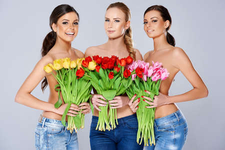 A trio of beautiful young women holding bouquets of fresh spring tulips in front of their chests as they smile at the camera photo