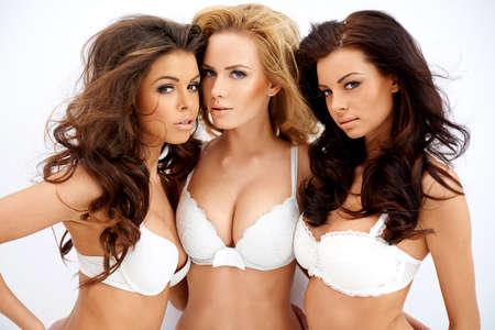 jungen unterwäsche: Drei sch�ne junge Frauen sexy kurvenreiche Modellierung wei�en B�stenhalter zeigen ihre gro�en Spaltungen, wie sie posieren Arm in Arm Blick verf�hrerisch in die Kamera Lizenzfreie Bilder
