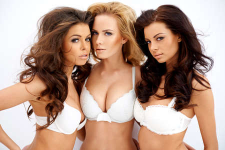 Three beautiful sexy curvaceous young women modeling white bras showing off their ample cleavages as they pose arm in arm looking seductively at the camera photo