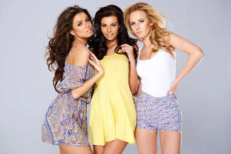 Three sexy chic young women in summer fashion standing arm in arm studio background Stock Photo