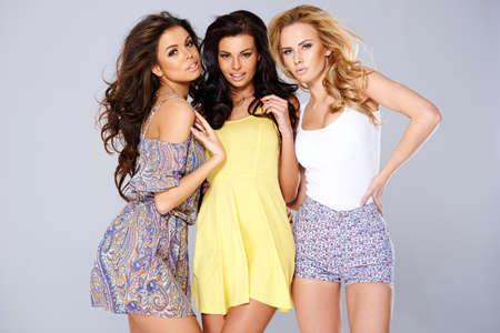 modelo hermosa: Tres mujeres j�venes elegantes atractivas en el brazo de pie de moda de verano en el estudio brazo fondo