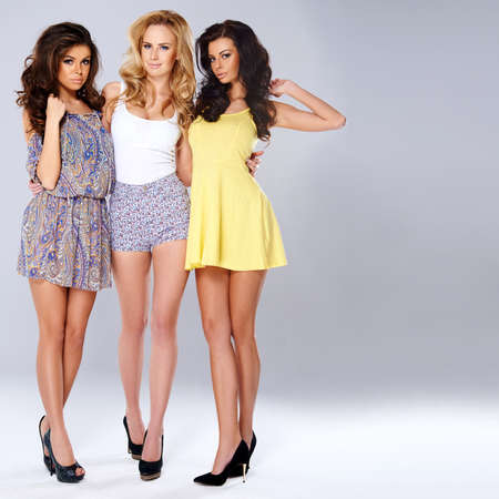 Three sexy chic young women in summer fashion standing arm in arm showing off their long shapely slender legs, studio background Standard-Bild