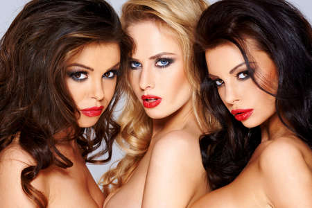 Trio of gorgeous sexy tantalising young women flirting with the camera with sensual seductive expressions photo