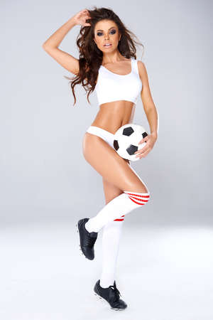 Sexy beautiful woman with long shapely legs in white lingerie, socks and boots posing with a soccer ball on a studio background