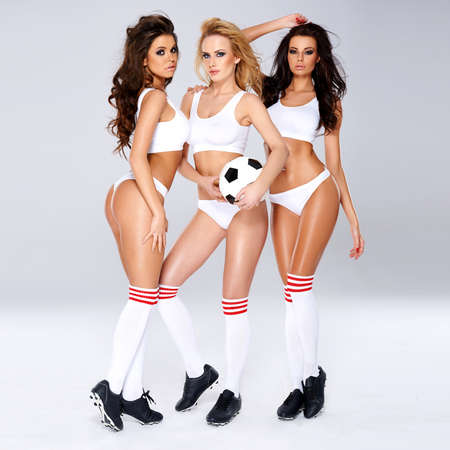 Three gorgeous enticing female football players wearing lingerie and boots posing together holding a soccer ball looking provocatively at the camera photo