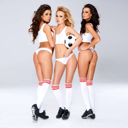 Seductive sexy female soccer players posing in lingerie, socks and boots seductively showing off their bare bodies while holding a soccer ball photo