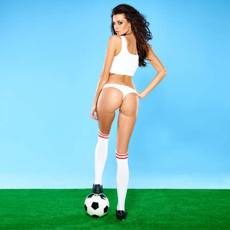 Beautiful busty woman soccer player with long curly brunette hair posing in lingerie with a soccer ball, blue and green studio background photo