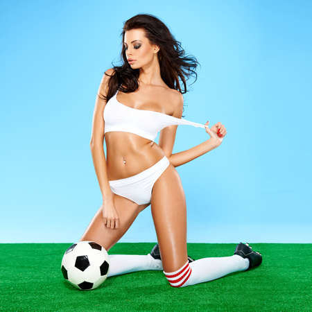 Sensual gorgeous brunette soccer player with a beautiful figure posing in white sports lingerie on her knees with a downcast flirting expression on a blue and green studio background photo