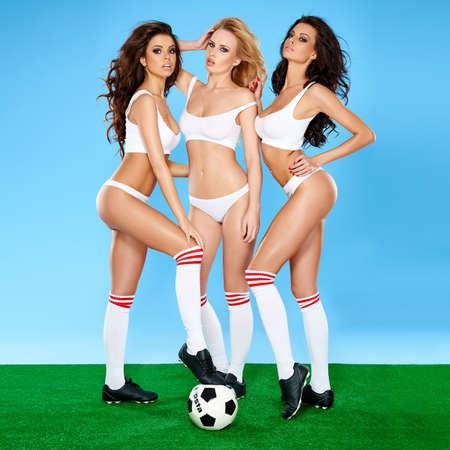 Three gorgeous beautiful sexy women soccer players posing seductively with a soccer or football in sports bras and panties showing off their shapely bodies on a green and blue studio background Stockfoto