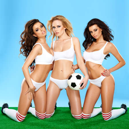 Three beautiful athletic sporty women in lingerie posing on\ their knees holding a soccer ball with alluring inviting looks on a\ green and blue background,