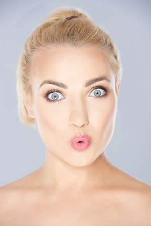 Beautiful young blonde woman looking surprised staring wide eyed at the camera with her lips parted  face portrait on grey
