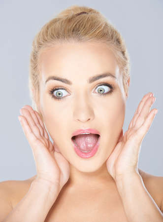 Beautiful blond woman with blue eyes with a shocked expression and her mouth open on a grey studio background photo
