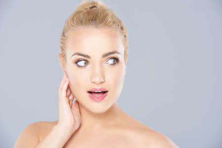 shocked face: Beautiful young blonde woman looking surprised staring wide eyed at the camera with her lips parted  face portrait on grey