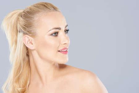cabelo amarrado: Vista cabe�a e ombros Side retrato de uma mulher bonita com longos cabelos loiros amarrados em um rabo de cavalo com l�bios entreabertos no cinza com copyspace