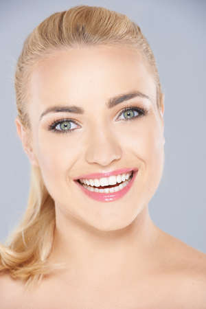 hair tied: Happy young blond woman with her long hair tied back and a beaming toothy smile looking directly at the camera  closeup face portrait on grey Stock Photo