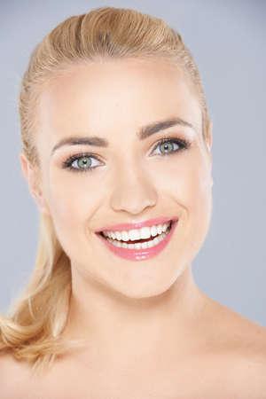 cabelo amarrado: Mulher loura nova feliz com seu longo cabelo amarrado para tr�s e um sorriso cheio de dentes radiante olhando diretamente para a c�mera retrato face do close up no cinza Banco de Imagens