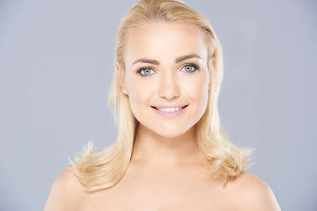 smooth skin: Beautiful blond woman with a lovely smooth fresh skin and bare shoulders looking directly at the camera with a smile  on grey Stock Photo
