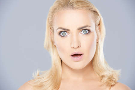 Beautiful blond woman with blue eyes with a shocked expression and her mouth open on a grey studio background